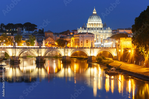 Poster Light pink Saint Angel bridge and Saint Peter Cathedral with a mirror reflection in the Tiber River during morning blue hour in Rome, Italy.