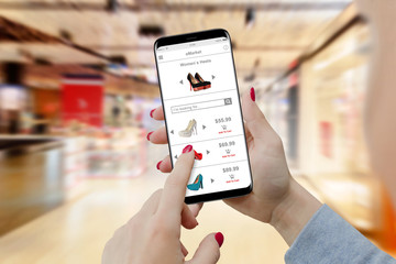 Girl searching heels online on her phone in shopping mall