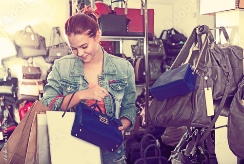 Fotobehang Art Studio Girl buying handbag in fashion shop