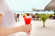 Young woman with tasty cocktail at resort