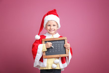 Cute Little Girl In Santa Claus Suit With Chalkboard Counting Days Until Christmas, On Color Background