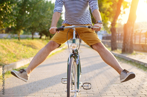 Foto auf AluDibond Fahrrad Close up of hipster man riding bicycle with his legs in the air