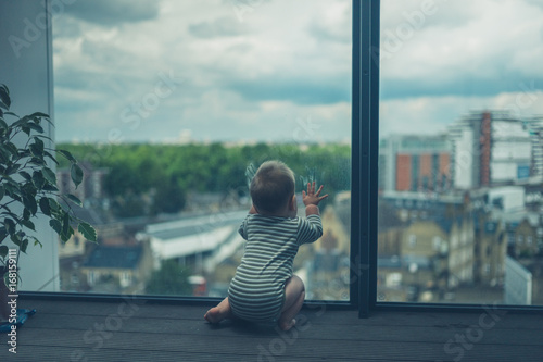 Photo  Little baby sitting on balcony in the city