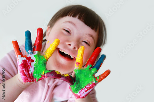 Photo  Cute little down syndrome girl with painted hands.