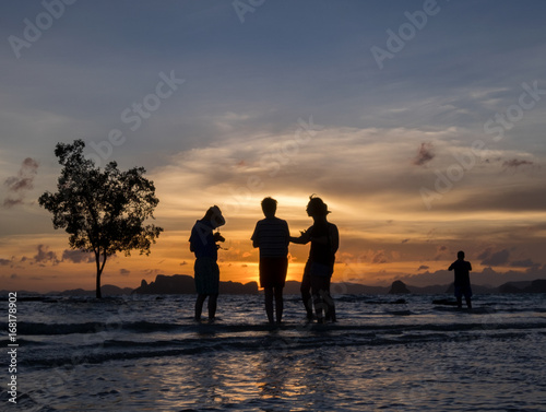 In de dag Duiken Silhoettes of people enjoying the sunset on the beach in tropical country, Krabi, Thailand.