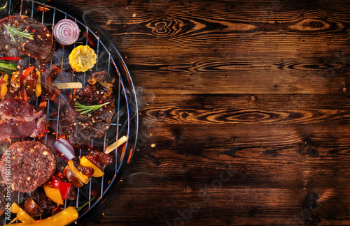 Photo Stands Grill / Barbecue Top view of fresh meat and vegetable on grill placed on wooden planks
