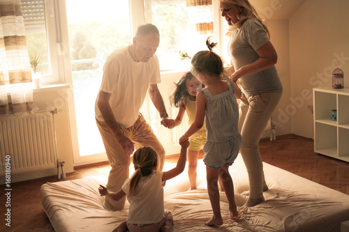 Fototapeten Tanzschule Grandmother and grandfather together with their granddaughters dancing on the bed.