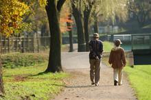 秋の公園を散歩する老...