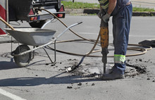 Asphalt Demolishing, Worker Using Jackhammer To Brake Pavement