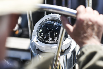 Fototapeta A compass, a view from above the steering wheel on a yacht.