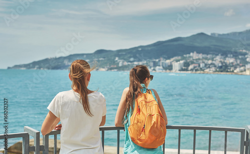 Fototapety, obrazy: Two young women, laughing girl with small orange backpack and her girlfriend stands on the pier on background of sea