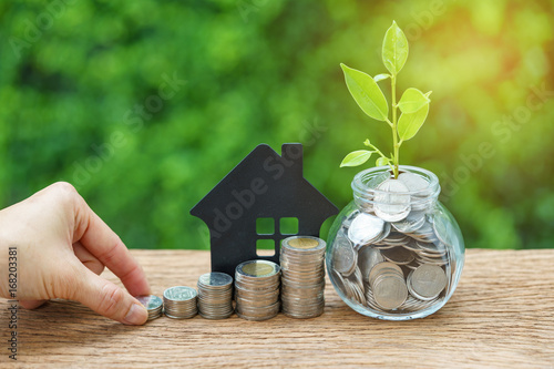Fototapeta growth sprout plant in jar with full of coins and hand holding stack of coins with paper house as property or mortgage investment concept obraz