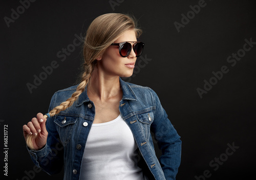 Fotografia, Obraz  Fashion model in sunglasses wearing denim jacket with pigtail looking aside