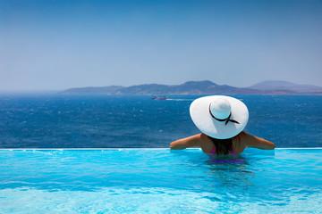 Fototapeta na wymiar Elegante Frau mit weißem Hut genießt die Aussicht von einem Pool auf das Meer