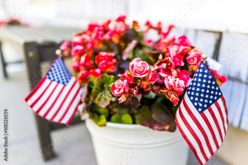 Patriotic flower pot with American flags and pink or red begonia flowers on porch