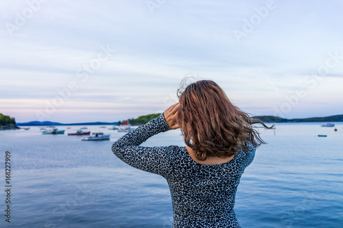 Photo  Young woman pointing to boats on edge of dock in Bar Harbor, Maine at sunset