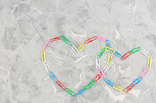 Two Heart Laid Out Of Colored Paper Clips On Old Gray Cement