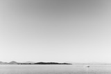 A small sailboat on a lake, with an island in the background, and a big, totally empty sky - 168232147