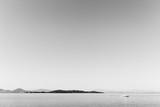 Mała żaglówka na jeziorze z wyspą w tle i wielkim, całkowicie pustym niebem - 168232147