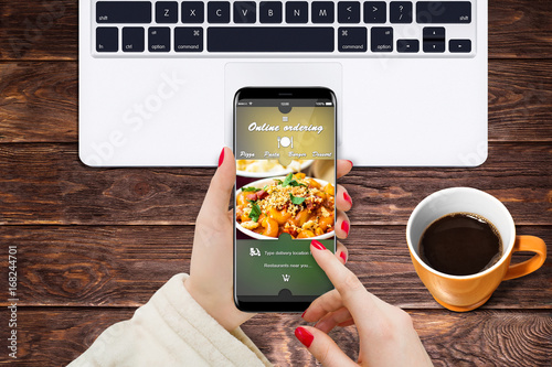 Girl at home ordering vegetarian food while sitting at desk in front of laptop and coffee © nikolas_stock