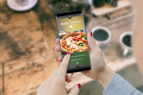 Girl ordering pizza with smartphone, while drinking coffee. Online order food concept © nikolas_stock