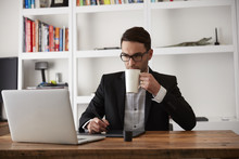 Caucasian Businessman Using Laptop And Digital Tablet Drinking Coffee