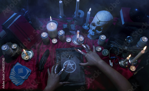 Fotomural Witchcraft composition with witch's hands, satanic magic books, skull, candles, tarot cards, crystal and amulets