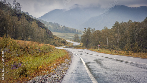 Landscape of mountains in the autumn day. Automobile winding road, leaving in the distance into the mountains between the green coniferous forest, the mountains of the Altai , sky in the mountains