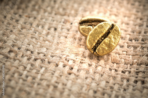 Tuinposter koffiebar Roasted coffee beans gold on sackcloth with copy space, The concept of luxury is extraordinary