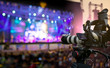 canvas print picture - Video production covering event on stage by professional video camera in outdoor concert at sunset