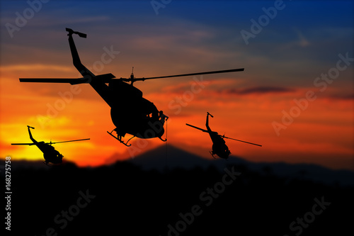 Tuinposter Helicopter soldier silhouette in rappelling climb down from helicopter on sunset with copy space add text