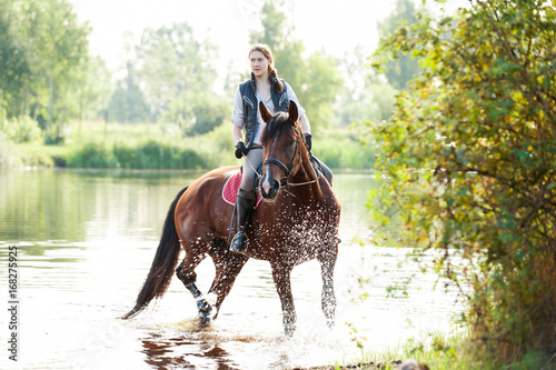Poster Equitation Young teenage girl riding horseback in river at early morning