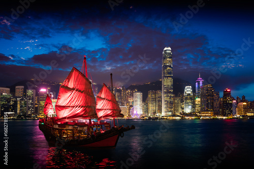 Plakat Victoria Harbour Hong Kong nocny widok z śmieciowym statkiem na pierwszym planie