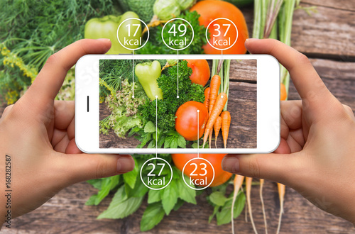 Leinwand Poster Smartphone in hand with information of calories in vegetables.