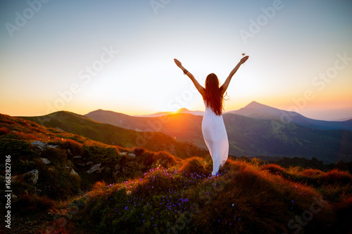 Hiker woman standing with hands up achieving the top. Girl welcomes a sun. Conceptual design. Successful woman hiker open arms on sunrise mountain top. Girl in long white dress in the mountains