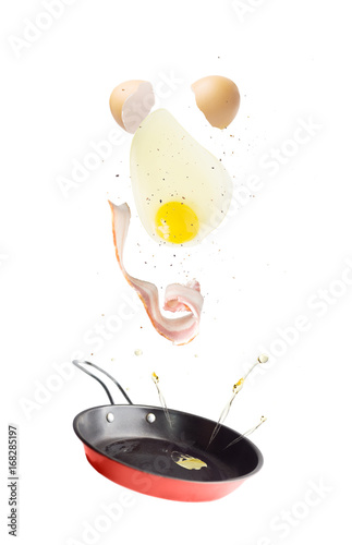 Flying pan with bacon, egg and ground pepper. Levitate breakfast ingredients