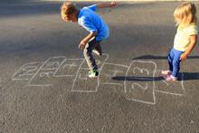 Kids Playing Hopscotch On Playground
