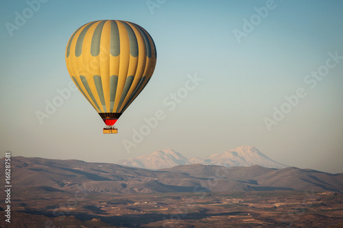 Poster Montgolfière / Dirigeable Balloon over Valleys of Cappadocia in background, aerial view