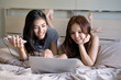 Girls friendship plan Hangout Traveling Holiday funny trip for this summer, checking popular places on laptop and smartphone on their bed