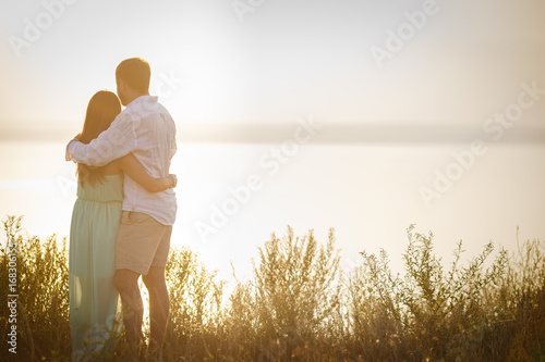 Husband And Wife Embrace Against The Background Of Nature Loving