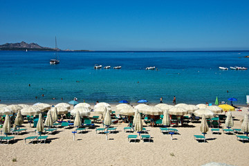 seascape of a sandy beach with deck chairs and beach umbrellas in front of a beautiful sea in Baia Sardinia.