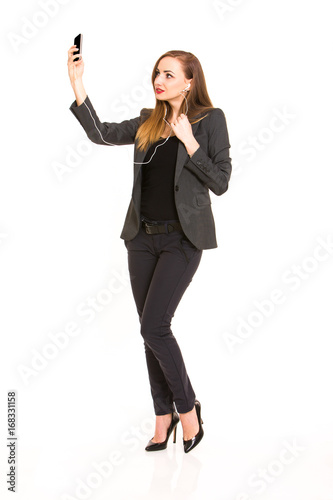 3f577bb3ccb1 Dark blonde beautiful woman wearing smart casual outfit and holding  smartphone and listening music on white background