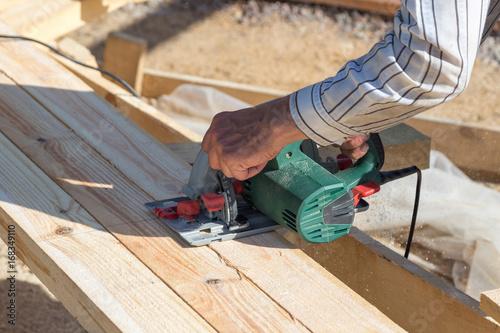 Fototapeta carpenter use electric saw to sawing wood obraz na płótnie