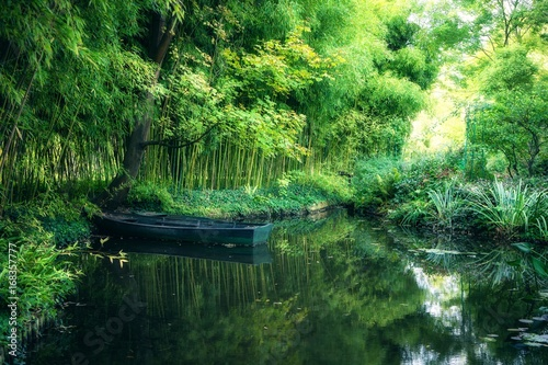 Foto  Claude Monet in autumn garden, boat in the lake among the bamboo groves