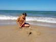 El niño esta jugando con arena en la playa