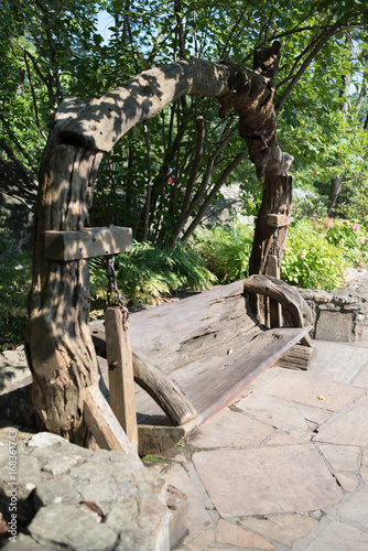 Tuinposter Oude verlaten gebouwen Wood Crafted Swing Bench in the Forest