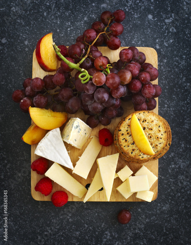 Valokuvatapetti Cheese, crackers and fruits on wooden background
