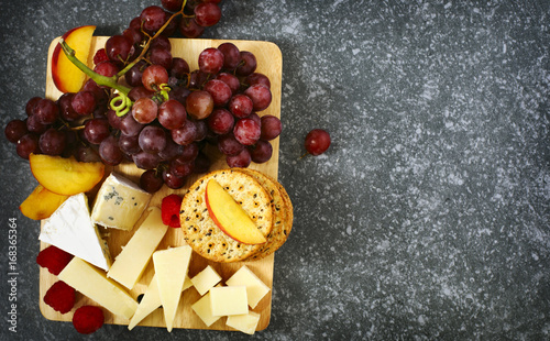 Cheese, crackers and fruits on wooden background Canvas-taulu