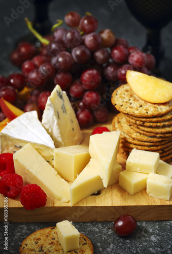 Valokuva  Cheese, crackers and fruits on wooden background