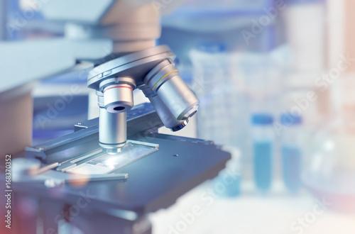 Fotografia  Scientific background with closeup on light microscope and blurred laboratory